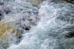 Powerful flow of water over the stones, mountain river close up. photo