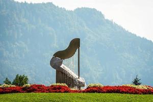 la fuente del arpa en ossiach, austria. bosque y montañas al fondo. foto