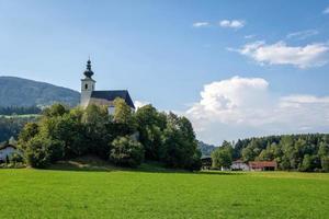 Village with a church in the Alpine valley near Salzburg. Austria photo