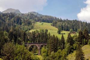 un pintoresco paisaje alpino con un antiguo puente ferroviario. Austria. foto
