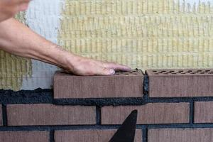 Trabajador de albañil instalando ladrillos en el sitio de construcción. foto