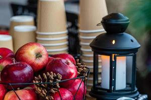 Linterna de velas incandescentes y canasta de manzanas sobre la mesa en el mercado de Navidad en Riga, Letonia, el enfoque selectivo foto