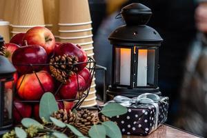 Linterna de velas incandescentes y canasta de manzanas sobre la mesa en el mercado de Navidad en Riga, Letonia foto