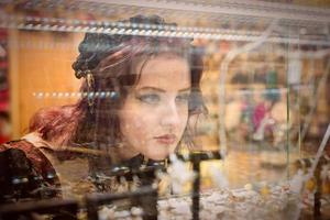 Young, a gorgeous redheaded woman dressed in retro fashion clothes, watches through the shop window of a jewelry store. photo