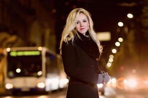 mujer hermosa, rubia en las luces del coche en la ciudad de noche. foto