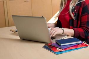 Blonde woman sitting at a laptop and writing. There is a laptop, a tablet, a phone and a notebook on the table. photo