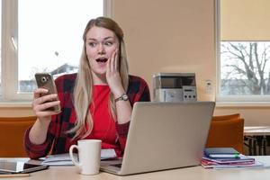 Smiling blonde woman, who is sitting at a laptop and surprised looks at the phone. photo