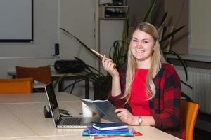 Smiling blonde woman sitting at a laptop drinking tea and working. photo