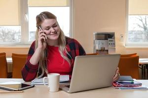 A smiling blonde woman sitting at a laptop and talking over a cell phone. photo