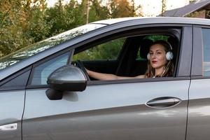A young, beautiful woman with long hair and headphones sits at the wheel of the car. photo