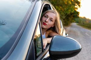 A young, beautiful woman with long hair sits at the wheel of the car and looks out the window. photo