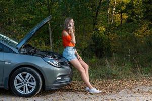 Bonita y joven mujer al borde de la carretera después de que su auto se descompuso - imagen foto