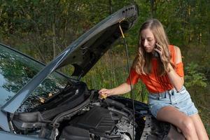 Mujer joven cerca de coche roto hablando por teléfono necesita ayuda - imagen foto