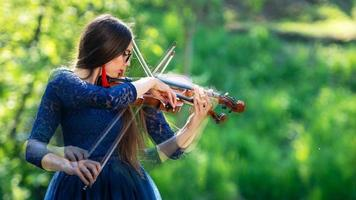 Creative composition. Young woman playing the violin at park. Shallow depth of field - image photo