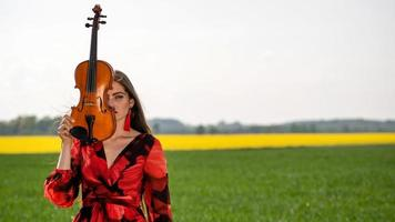 Portrait of a positive young woman. Part of the face is covered by the neck of the violin - image photo