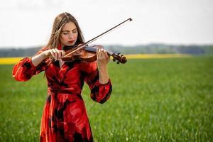 Mujer joven en vestido rojo tocando el violín en la pradera verde - imagen foto