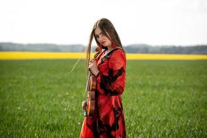 Young woman in red dress with violin in green meadow - image photo