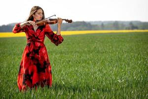 Young woman in red dress playing violin in green meadow - image photo