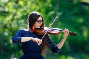 Young woman playing the violin at park. Shallow depth of field - image photo