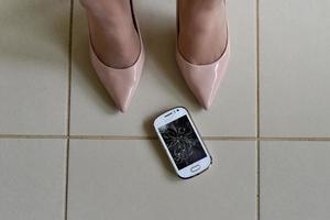 teléfono inteligente roto en el piso de baldosas foto