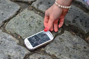 teléfono inteligente roto en el suelo foto
