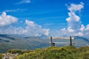 A wooden bench at the top of the Alps photo