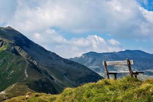 un banco de madera en la cima de los alpes foto