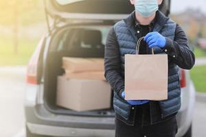 Repartidor recortado con gorra roja, máscara médica facial y guantes sujetan una bolsa de papel cerca del automóvil al aire libre. servicio coronavirus. las compras en línea. Bosquejo. foto