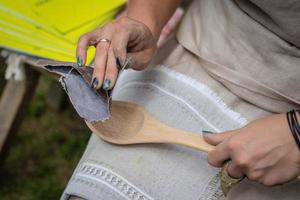Woman making traditional handcraft wooden spoon photo
