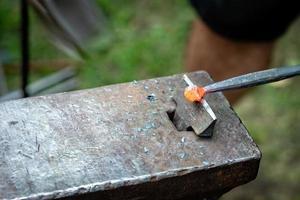 Herrero forjando una tira de metal caliente foto
