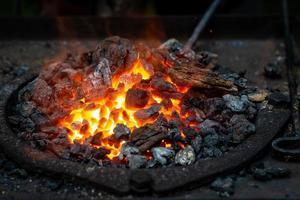 Blacksmith forging a strip of hot metal photo