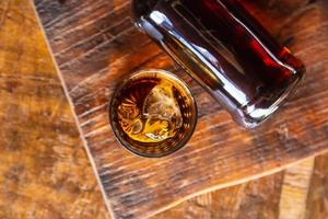 Liquor glass and decanter on wooden table photo