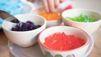 la gelatina de pipo de colores cortada en trozos pequeños en una taza pequeña está lista para hacer postres para los niños. foto