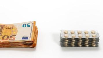 Medicamentos y billetes de euro aislados en blanco foto