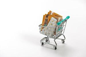 Shopping cart with pills and Euro banknotes photo