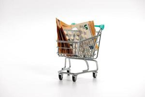 shopping cart with tablet blisters and euro banknotes, expensiveness of medicine concept, isolated photo