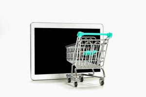 Mini shopping cart and digital tablet with black screen photo