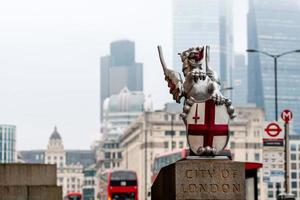 una escultura de dragón con el escudo de armas de la ciudad de londres en el puente de londres. rascacielos borrosos y autobuses rojos de dos pisos en el fondo. foto