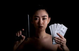 Asia woman one hand holding a gun and money at the black background photo