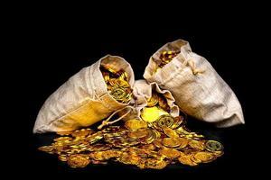 apilar monedas de oro en el saco del tesoro foto