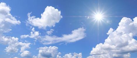 Beautiful clear blue sky with white clouds and sun photo