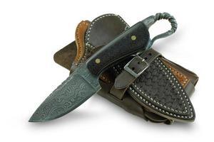 Paquete doble de cuchillo de Damasco en la funda de cuero y funda de teléfono sobre fondo blanco. foto