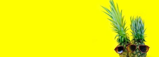 Pineapple wearing red sunglasses on isolated yellow background photo