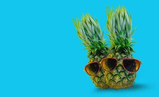 Pineapple wearing red sunglasses on isolated blue background photo