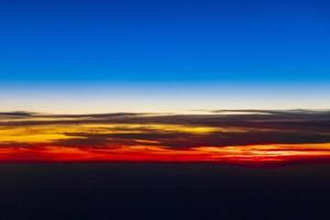 Flying over Europe to Mallorca at beautiful colorful sunset. photo