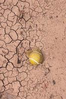 Pelota de tenis amarilla en el suelo del desierto foto