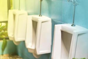 Fila de urinarios blancos en el baño masculino foto