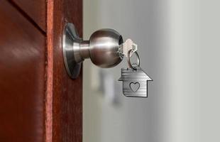 Puerta abierta con llaves, llave de la casa en el ojo de la cerradura con casa pequeña foto