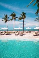 Chair pools or beds and umbrellas around swimming pool with sea background - Holidays and vacation concept photo