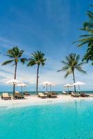 Piscina de sillas o camas y sombrillas alrededor de la piscina con fondo de mar - vacaciones y concepto de vacaciones foto